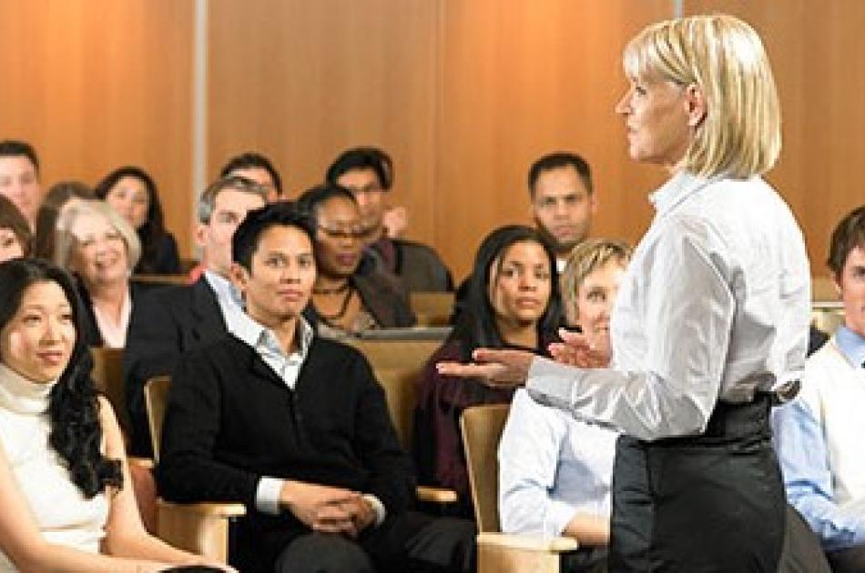 Woman in white shirt lecturing in front of students