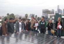 Volunteers gathering around a solar power panel.