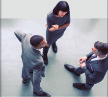 2 guys and a girl in business attire standing facing each other discussing
